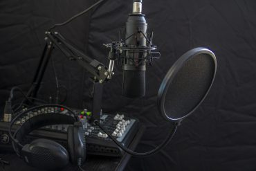 A podcast setup showing a mixer, microphone and headphones