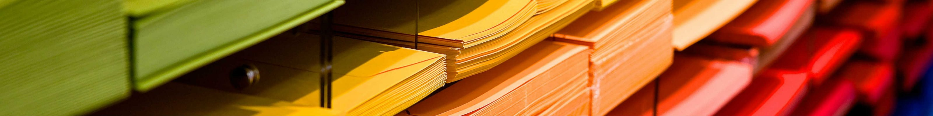 Piles of paper organised by colour