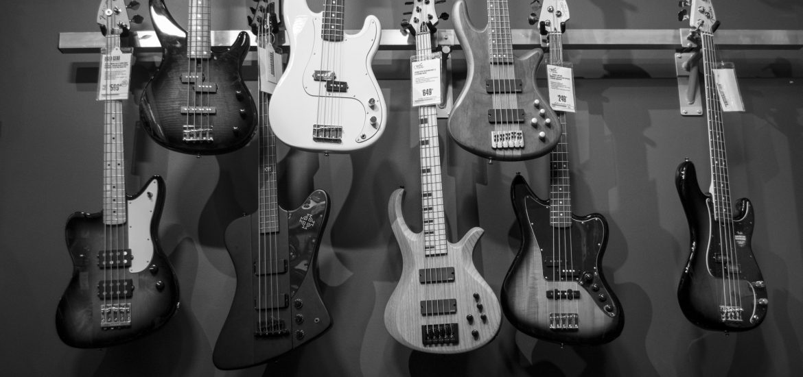8 bass guitars hanging on a shop wall