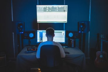 An engineer sat at a desk with two sets of studio monitors