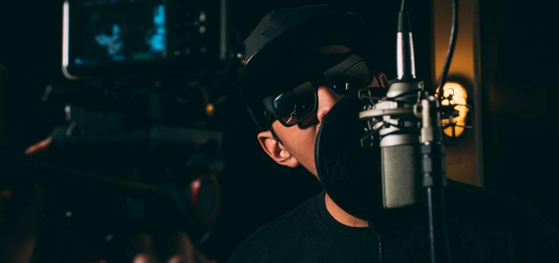 A rapper recording vocals in the studio