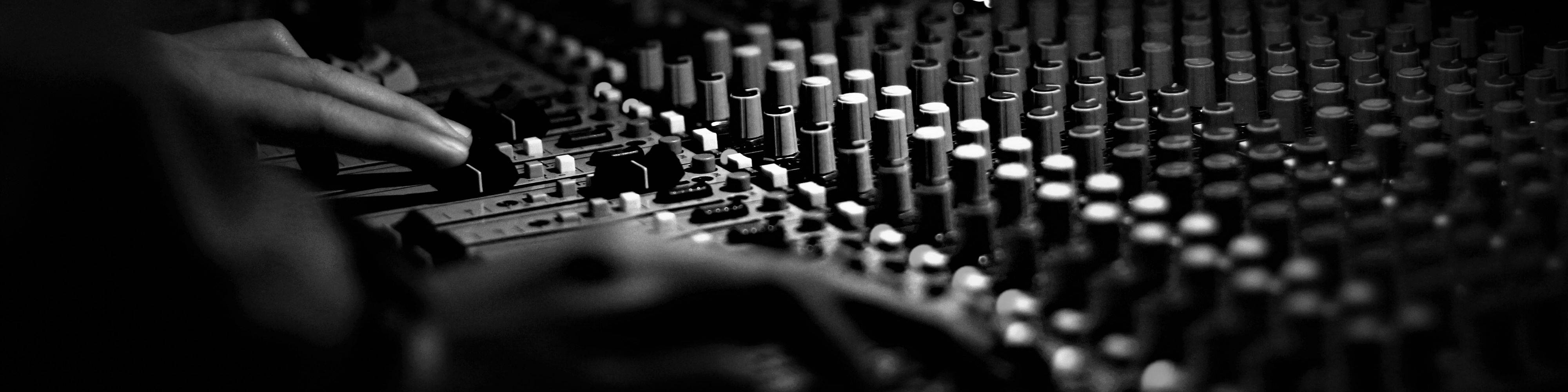 Two hands on a mixing desk