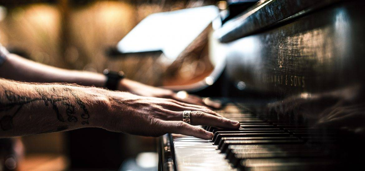 A pair of hands on an upright piano