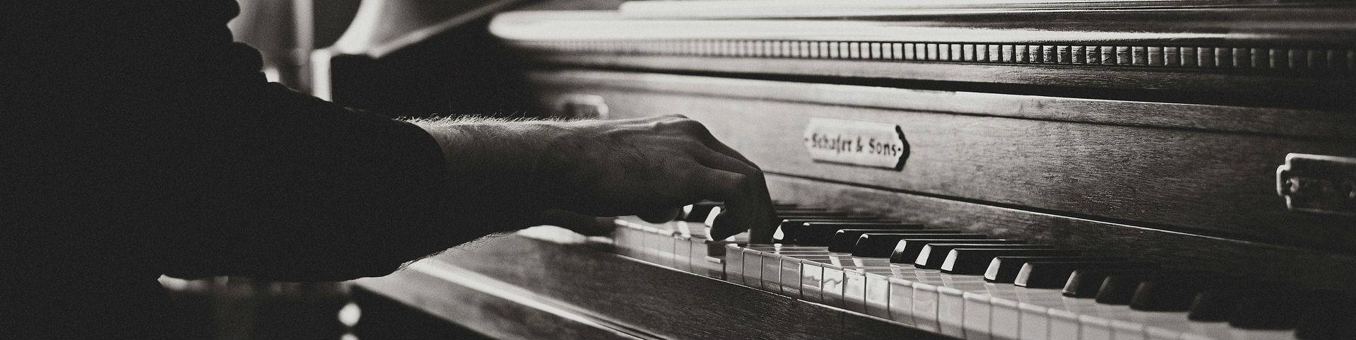 A black and white image of hands playing a piano